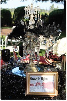 Estilo glam rock en una mesa de bienvenida. Grandes candelabros con cristales y negro, mucho color negro para unas decoraciones de salones muy atrevidas.