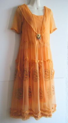 Peach crepe silk two-piece 1920s dress. Under dress is matching peach on the top part with shoulder straps separated from the sleeves followed by a pink sash and a mandarin orange skirt. Sleeves have a ruffled finish with metal filigree edging.