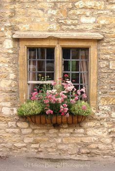 Stone façade and gorgeous paned window with window box.