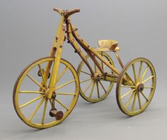 Boneshaker velocipede bicycle, unknown maker, age unknown (?1860). Appears to be blacksmith made. Wooden frame and wheels with wrought iron bracing and carriage bolt fasteners. Old chrome yellow paint. 27″ Front, 23″ rear wheels. 57″ L. x 26″ W. x 42 1/2″ Ht. x 27″ seat Ht.