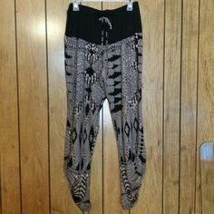 Dressy joggers nwot Elastic waist with decorative tie, solid back across tummy area. Black and light purpleish Aztec design on legs. The bottom outside seams have elastic inserts for a shirring effect. Looks amazing with heels or flats, or Short boots. Size L but looks good on med too. I wear a 10 and these are just loose enough to drape nicely. Love them and have 2 pairs myself. New Lime & Chili Pants Track Pants & Joggers