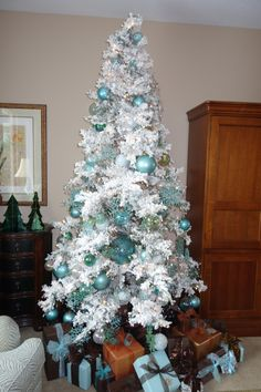 White Flocked Christmas Tree with turquoise, Copper and Brown wrapped gifts!  Ready for Christmas.