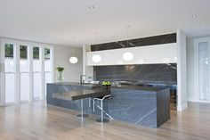trendsideas.com: architecture, kitchen and bathroom design: Competitive edge - The kitchen, which was manufactured by Hewe Kitchens & Interiors, features a long island with a cantilevered solid oak slab, which serves as a focal point for entertaining. The marble is from Italian Stone, and the stainless steel from SJ Crosbie Stainless Steel.