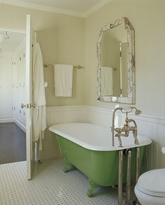 Lovely vintage kitchen design with green claw foot tub, chair rail and beadboard and butter yellow walls paint color.