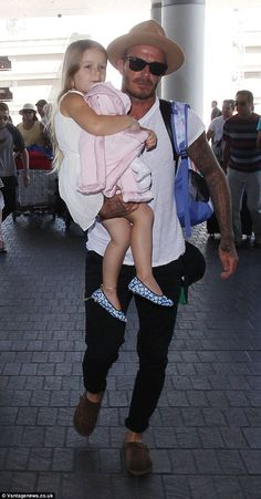 David Beckham, 40, was seen cradling his four-year-old daughter Harper, as he arrived with...