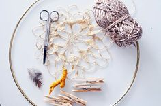 Supplies you'll need:  Large metal loop (wire macrame hoop) Lace doily — Find them at a thrift store, flea market, or on Etsy. (Thinner fibers like doilies made of mercerized cotton work the best.) Small ball of inexpensive, lightweight yarn (Use a cotton/poly blend for less fray.) Clothespins or clips Decorations (feathers, shells, stones, gems, trinkets, jewelry pieces)