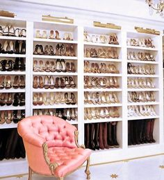 Amazing shoe closet features brass picture lights illuminating shelves for shoes and boots alongside salmon pink tufted French chair.