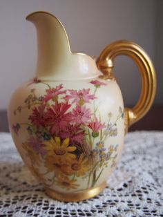 Royal Worcester Blush Ivory Flatback Jug.  Hand painted pink and yellow daisies, little blue flowers with yellow centers and green foliage. Gold gilded handle and bottom rim. Circa 1896