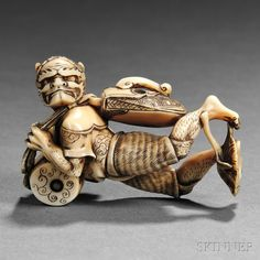 Ivory Netsuke of an Oni, Japan, 19th century, standing in an acrobatic pose with a Japanese drum on his chest, carrying a satchel on his back, a lotus leaf branch near his feet, unsigned, ht. 1 3/4 in.
