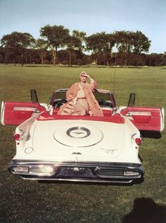 Anne St. Marie in fur-lined coat by Maximilian is sitting in a 1957-58 Chrysler Imperial convertible, Vogue November 15, 1957