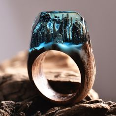 """WATERFALL is a ring made with light oak, light blue jewellery resin and white """"snow"""" that glows in the dark. Every day is an intimate escape."""