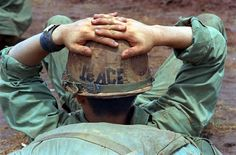 "With a helmet declaring ""Peace,"" a soldier of the 1st Cavarly Division, 12th Cavalry, 2nd Battalion, relaxes June 24, 1970, before pulling out of Fire Support Base Speer, six miles inside the Cambodian border. The troops were returning to South Vietnam after operations against enemy sanctuaries in Cambodia. (AP Photo)"