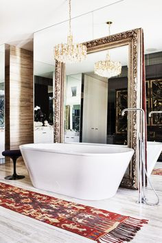 Stunning framed mirror in bathroom with large white tub under a beautiful chandelier.
