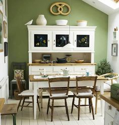 Green, white and brown dining area with an eclectic collection of chairs and an enormous practical buffet and hutch.