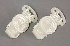 A pair of Chinese white jade belt Ornaments, Qianlong (1736-1795), each in the form of a two-handled vase on an openwork stand, the centre of each vase carved with a flowering prunus branch within a recessed panel beneath a band of leaves on the neck, the stone of even white colour, 6.5 cm long 5 November Sale £3000-4000