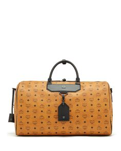 """MCM """"Nomad"""" weekender bag in Visetos coated canvas. Rolled top handles with buckle clasp. Removable and adjustable shoulder strap. Luggage and ID tag hangs from front. Two-way zip top. Interior slip a"""
