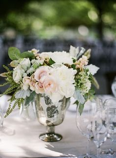 I like that these centerpieces are low, and that they're in glass, but not necessarily a vase. Also, I like the look more or less, but without the pink.