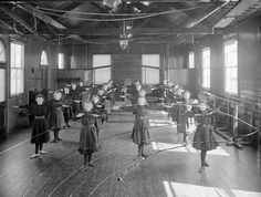 Exercise formed an important part of the school day in the early 1900s. Exercise was set to music and some were designed to be done while sitting at a desk. This group of girls is from the Ursuline Convent in Waterford.    Format: Glass Negative