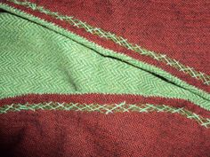 double herringbone stitch as decoration on a kaftan. sewn with threads pulled from remnants of the green fabric used on the reverse side