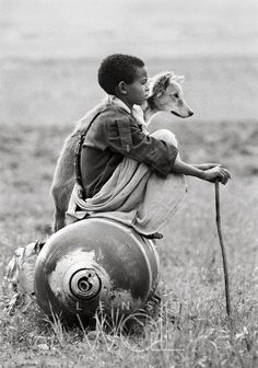 A Young boy sitting on an unexploded bomb dropped by Mengistu forces in Tigray, north Ethiopia. Photo by © Dario Mitidieri. Black N White, Black White Photos, Black And White Photography, Jolie Photo, People Of The World, Beautiful Children, Beautiful Dogs, Mans Best Friend, In This Moment