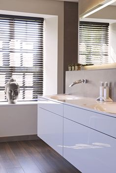 The large double vanity used in this design is wall hung to create floating effect. It provides great storage and the finish reflects the light beautifully which adds to the tranquil theme of this design. A full width wall mirror has been fitted into a recess and back lit to create a calm, soft light.  Designed by David Aspinall  SOUTH DEVON I Sapphire Spaces | Sapphire Spaces - Image Alt