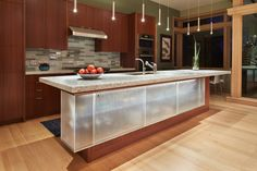 #kitchen #kitchenisland | DESCHUTES-House-Finne-Architect-9 | The kitchen island has a suspended glass cabinet that's outfitted with LED lighting adding a new spin on traditional islands