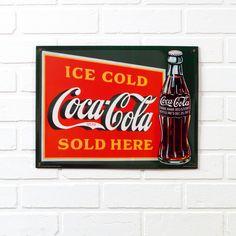 Esprit rétro pour cette plaque en métal décorée aux couleurs de la marque Coca-Cola®.