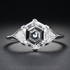 $39,500 USD A uniquely beautiful Art Deco diamond engagement ring featuring an entrancing and enchanting hexagonal-cut diamond weighing just nine points shy of three carats. This rare and radiant rock is set with chevron-shape prongs between a sparkling pair of triangle diamonds set flush in the sleekly tapered platinum shoulders. The ring of a lifetime!