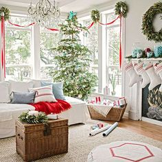 Create a rustic holiday living room with simple, natural accouterments like grain-sack stockings, olive leaf wreaths, and pops of French blue in the pillows, on the mantel, and throughout the Christmas ornaments. For an easy furniture transformation, cover your sofa and chairs with linen sheets -- tres chic!/