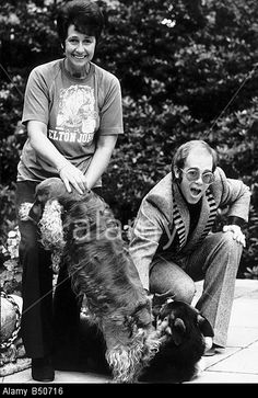 Elton john with his mother and two dogs on patio