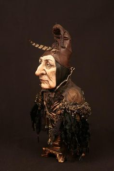 Aztharot  Keeper of the keys, potions and spell books.  Costumed in leather cape and hat with a single feather.  14 INCHES (35.56 CM) TALL  Paper clay, acrylic paint,  leather, pheasant feather, miniature brass keys, antique trims.