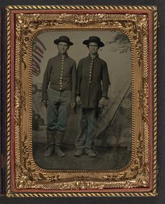 [Two unidentified young soldiers in Union uniforms in front of painted backdrop showing military camp]
