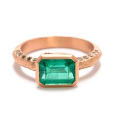An alternative, unconventional wedding ring; a client wanted to use an emerald from her mother's ring but did no want it to look like an engagement ring, but something modern and funky. Page cast the ring in 18KT rose gold and added black diamonds on the side with a window bezel.