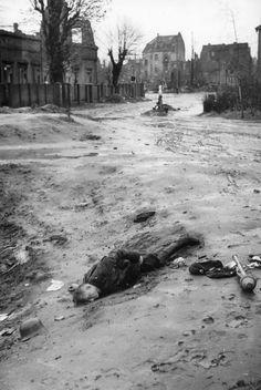 dead Volkssturm soldier lies next to his Panzerfaut in a town in German, 1945.