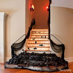 Try a clever way to keep ghoulish guests on the ground floor Let guests know the upstairs is off-limits during the party and decorate the staircase at the same time. We draped black cheesecloth and black leaf garland across several lower stairs and added hair-raising black rats. To complete the look, line up small flameless candles along each step.