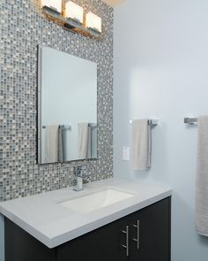 Mosaic tile adorns the wall above the sink for a chic and modern appearance.