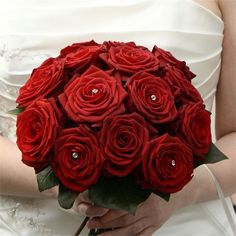 Nevenka ordered her wedding flowers from Flower Frenzy in Worsley. She chose a selection of deep red and ivory roses, and for her bridal bouquet she carried an arrangement of red roses, with diamante centres in every other bloom.The church was decorated with floral arrangements made by a member of the church's congregation. These were then carried up to the hotel later on. The tables at the venue were decorated with red roses in glass bowls, organised by professional venue dressers.