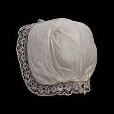 Infant's cap, North America, second quarter 18th century. White linen, forehead band and band extending down center back of cap crown embroidered with white linen thread in design of flowering stems with ornamental blossoms and leaves, seams hemstitched and trimmed with fine white linen herringbone stitch, fullness gathered at top of cap crown and by drawstring at back of cap crown, edged with bobbin lace.
