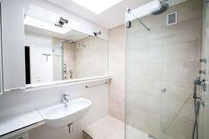 Waschbereich mit flachen, länglichen Waschbecken und sehr großem Spiegel, links daneben ein Hängeschrank