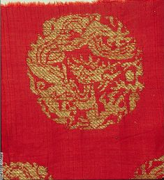 Zoom in of the textile with Coiled Dragons, Jin dynasty (1115–1234), China. Plain-weave silk brocaded with metallic thread; This textile represents the tradition of northern China's Jin dynasty, which was known for textiles brocaded in gold with offset asymmetrical motifs on a solid-colored background. The motif here is a coiled dragon with a flaming jewel.