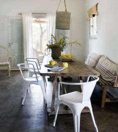 in this beach house in Fueteventura the owners cleverly balance rustic details, like the hanging basket lampshade, with modern touches like these classic aluminium chairs... (and the table is a repurposed market stall!)...LOVE THE LOOK