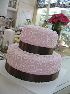 Pink fondant cake with brown ribbon and  white piping.  Was made for a classy baby shower, but would be great for many other occasions as well!