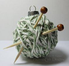 glue the end of yarn on a round ornament, begin wrapping, glue a few times as you go, glue the end, tuck knitting needles made from cut skewers with round beads glued on the ends