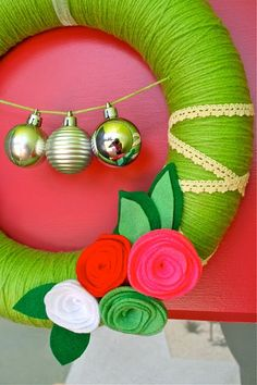 Love this idea for stringing ornaments across wreath. And this color combination! #yarn #wreath