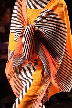 Issey Miyake 2013SS graphic bold stripe print black and white with pop colour of orange drape and trouser