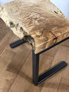 This one-of-a-kind live edge wood table is handcrafted from a solid 3 thick piece of quilted maple. The table top is supported by a pair of simple c-style steel legs. The legs are constructed out of 2 steel tube pipe that has been primed and painted in a black stainless steel to