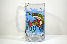 Fishing Beer Mug - Beer Glass - Muskie Fish - Fishing Gift - Gifts for Men. This hand painted beer glass features a frenzied fish being lured in by the bait of a fisherman. These make memorable gifts for outdoorsy types that love to fish. The transparency of the glass paint gives off gorgeous stained glass effects and the colors vary depending on the light or the liquid in the glass. Have this unique beer glass personalized with a name, date or short quote. ❤️ Glass holds 25 oz ❤️ Each…