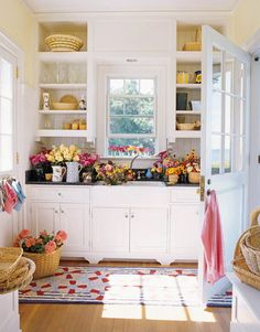 The mudroom multitasks for flower arranging, with open shelves that store baskets and the owner's pitcher collection. Beadboard and an oversize porcelain farm sink create the feeling of turn-of-the-century Martha's Vineyard. Resilient navy-blue granite countertops keep watermarks at bay and oak floors have a light pine stain so sand doesn't show Lighthouse area rug by Claire Murray.