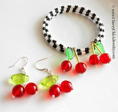 Cherry Earrings because theyre just that cute. Get your Rockabilly going with these bright red jewels on your ears. Whimsical earrings created with Czech glass druk beads and Czech pressed glass leaf beads. The earrings measure 1.75 in length. This listing is for one pair of Cherry