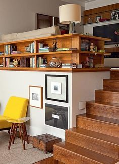 Na sala em desnível, a designer de interiores Marília Campos Veiga transformou um lado do guarda-corpo em estante